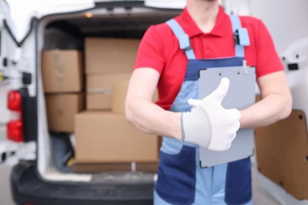 제복을 입은 로더 드라이버는 상자가있는 자동차의 배경에 엄지 손가락을 들고 있습니다.