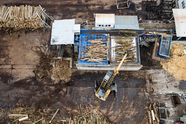 A loader loads logs at a wood processing factory from above from a drone