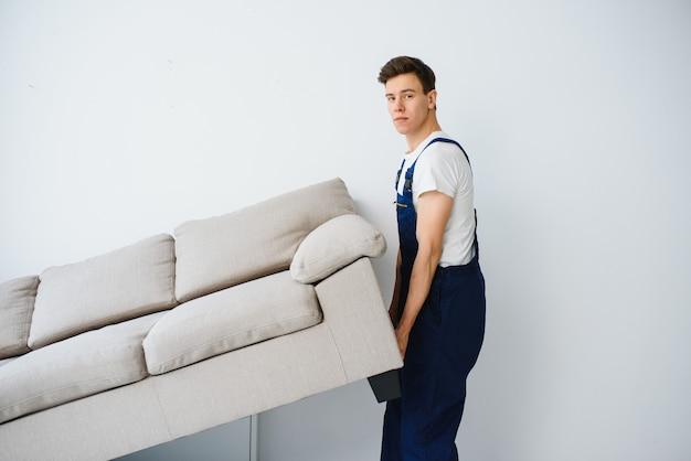 ローダーはソファ、ソファを動かします。オーバーオールの労働者はソファ、白い背景を持ち上げます。配送サービスのコンセプト。