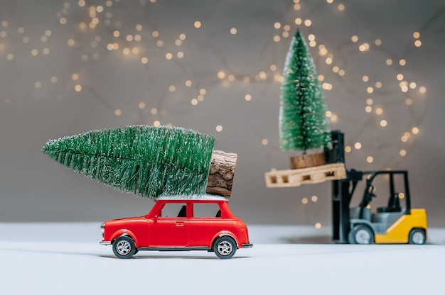 A loader and a red retro manina are carrying green trees. against the background of festive lights. concept on the theme of christmas and new year.
