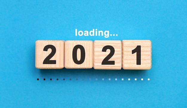 青い背景の上の木製の立方体に2021年を読み込んでいます