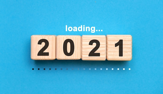 Loading 2021 years on wooden cubes on a blue background
