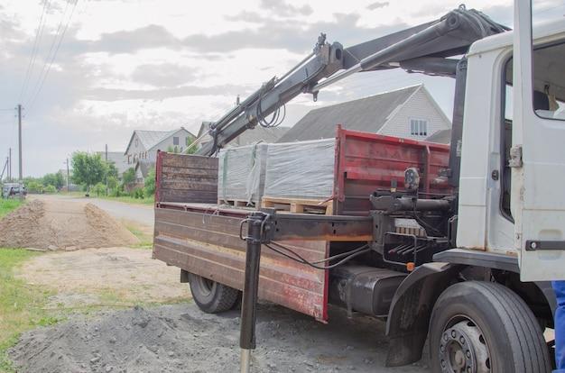 포장용 슬래브가 있는 팔레트를 트럭에 싣습니다. 자동차에서 바닥에 타일을 로드합니다. 건축 자재를 집으로 배달 및 하역. 트럭 크레인이 도로 타일을 내리지 않았습니다.