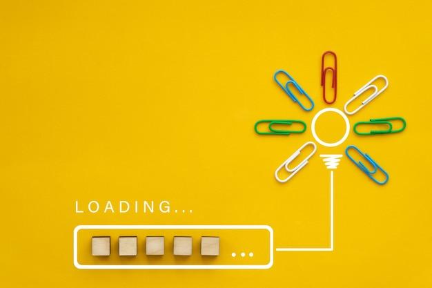 黄色の背景の電球で処理されたアイデアビーがほぼ完成したローディングバー