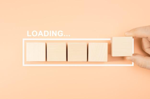 パステルカラーの背景に木製の立方体のバーを読み込んでいます。ロードバーの進行状況に「loading」という単語が含まれる木製ブロック
