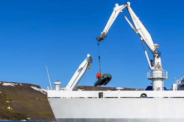 Погрузка надувной лодки с водителем на палубу с помощью судового крана. арктическая экспедиция.