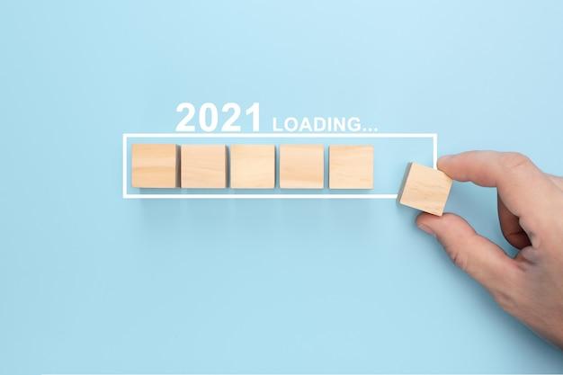 プログレスバーに木製の立方体を手で置くことで新年2021をロードします。新年の創造的な背景。