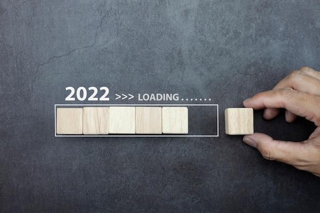새해 2022년 개념 손 남자가 프로세스 막대에 큐브 나무를 놓는 것을 로드합니다.