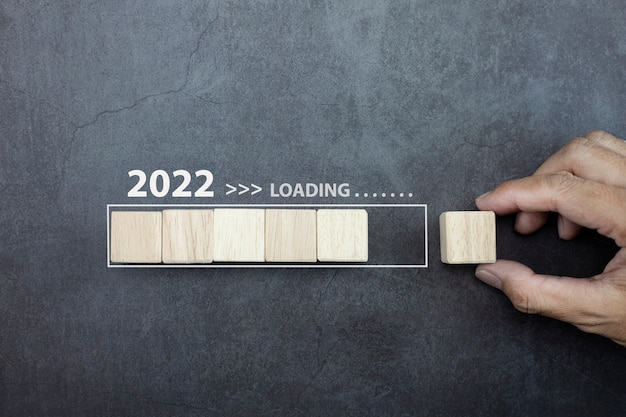 Loading new year 2022 concept hand man putting cube wooden on process bar