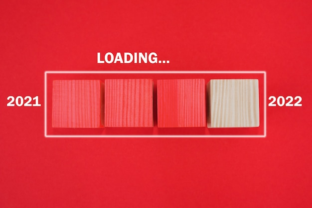 Loading new year 2022, start text on wooden cube, thinking goal concept. a new beginning. red background.