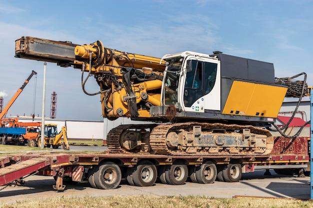 Погрузка буровой установки для установки буронабивных свай на трал для транспортировки к месту работы. мощная строительная машина. фундаменты свайные.