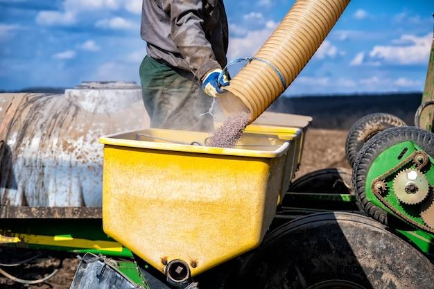播種ユニットのホッパーへのミネラル肥料の投入。