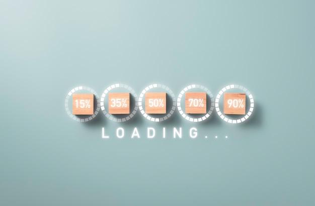 Загрузка процентного экрана печати на деревянном кубическом блоке с синим фоном, загрузка электронной загрузки и прогрессивная концепция бизнес-проекта.