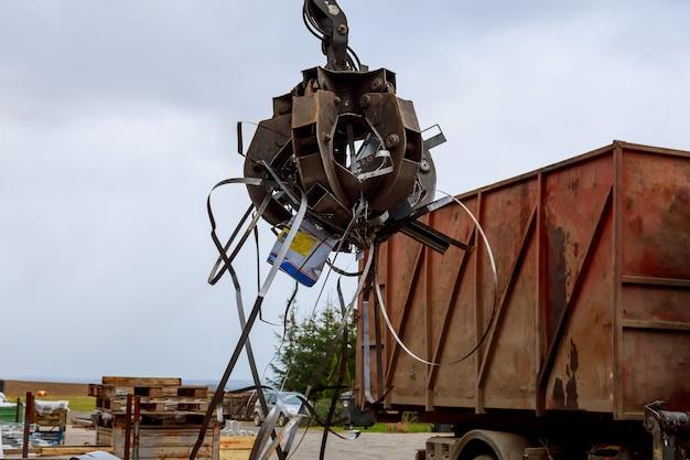 고철을 트럭에 싣기 크레인 그래버 도크에 녹슨 금속 스크랩을 싣는 그래플 트럭이 재활용을 위해 산업 금속 스크랩을 싣습니다