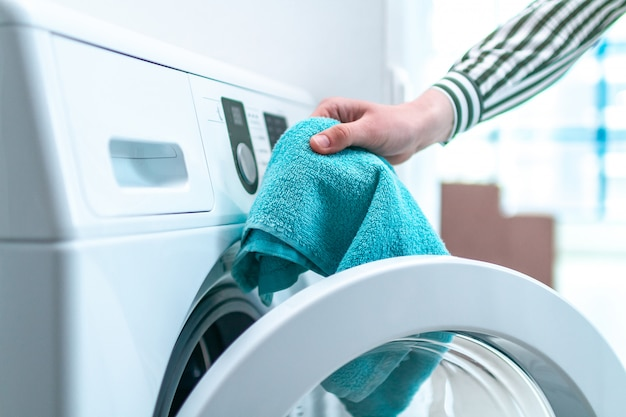 Loading towel, clothes and linen in washing machine. doing laundry at home. household chores and housekeeping