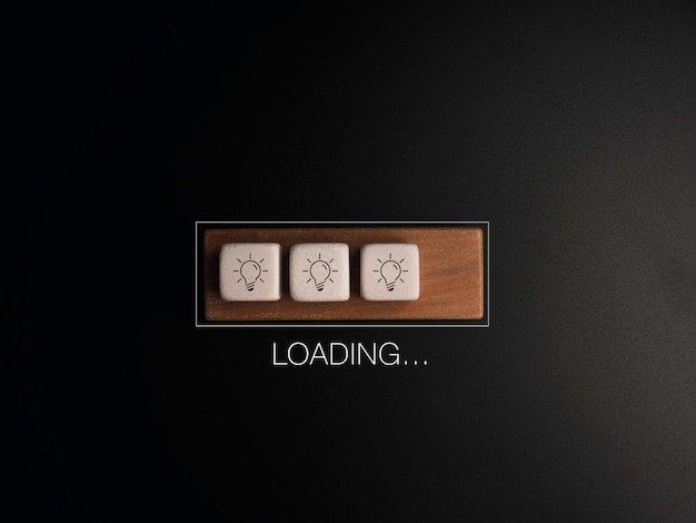 Loading..., the word with light bulb icon on white dices and wood cube block in the progress bar on dark background. update and upgrade ideas, creative thinking concepts.