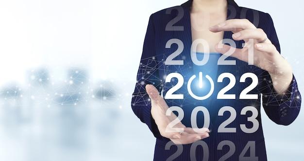 2021년부터 2022년까지 로드 중. 개념을 시작합니다. 밝은 배경이 있는 가상 홀로그램 2022 아이콘을 들고 있는 두 손. 2022년을 환영합니다. 비즈니스 새 해 카드 개념입니다.