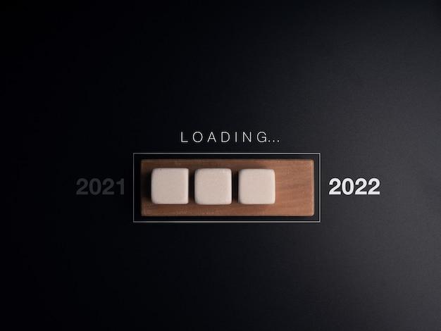 年の概念を読み込んでいます。木製のプログレスバー、暗い背景の単語と白い立方体のブロック。何かを更新したり、アイデア、創造的思考の概念をアップグレードしたりするためのビジネス。