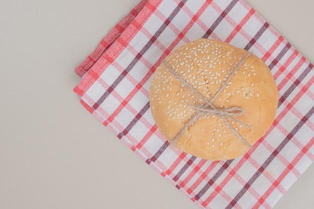 テーブルクロスの上にロープでハンバーガーパンをパン