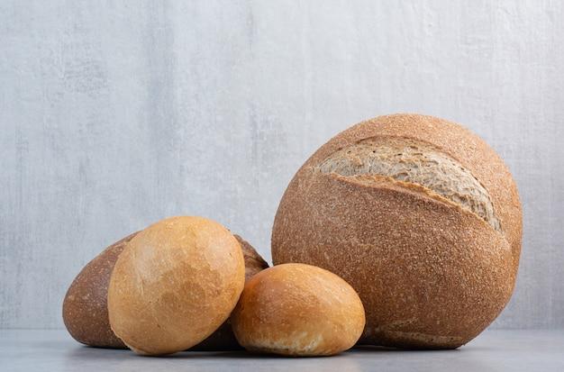 Буханка и кусочки хлеба на мраморном фоне. фото высокого качества