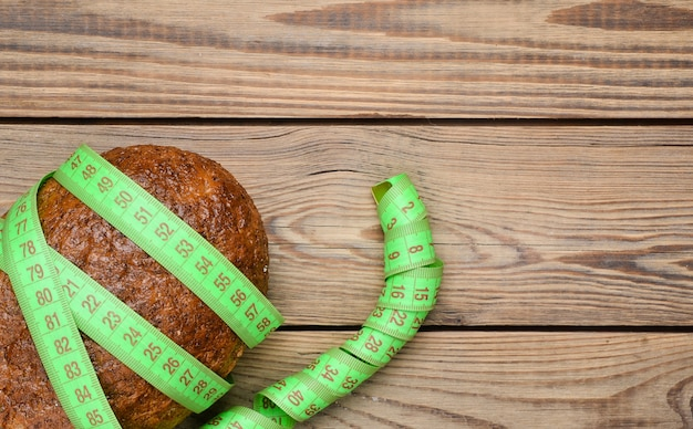 A loaf of bran bread wrapped with a ruler on a wooden table. the concept of healthy eating, losing weight. top view.