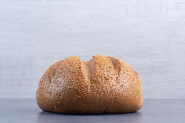 Pagnotta di pane ricoperta di semi di sesamo su fondo marmo. foto di alta qualità