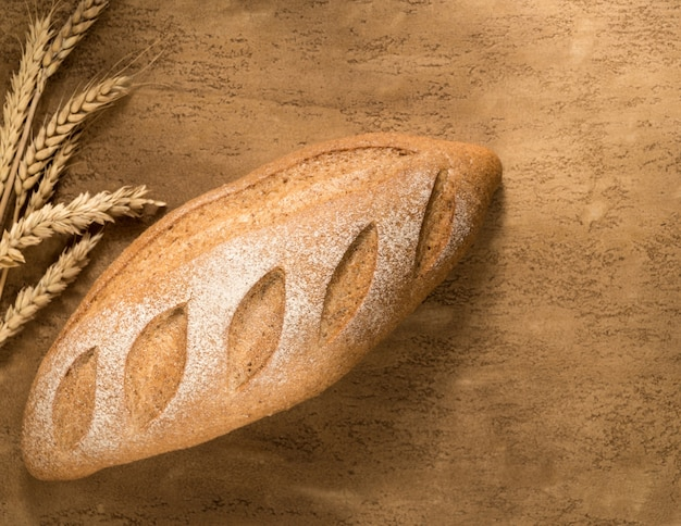 A loaf of bread and a golden spike on the plastered surface, top view