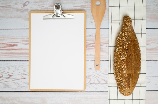 Loaf of bread on napkin; spatula and paper on clipboard over the wooden desk
