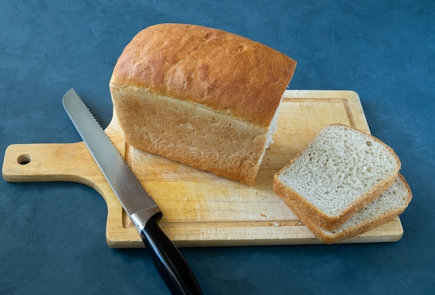 A loaf of bread, slices cut from it and a knife lie on a wooden cutting board. horizontal orientation, selective focus.
