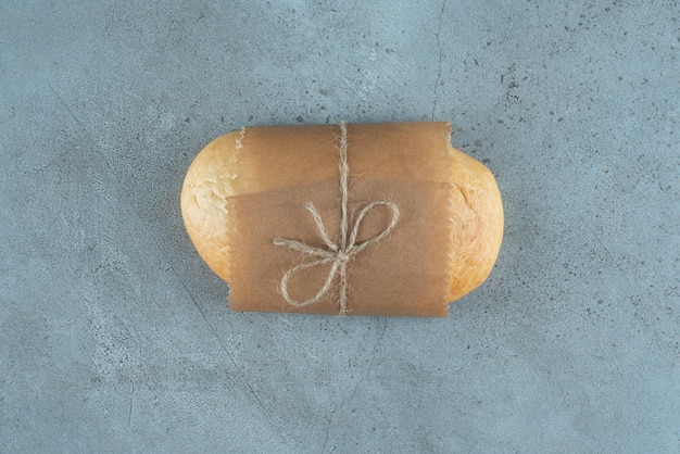 Loaf of bread tied with rope on marble surface.