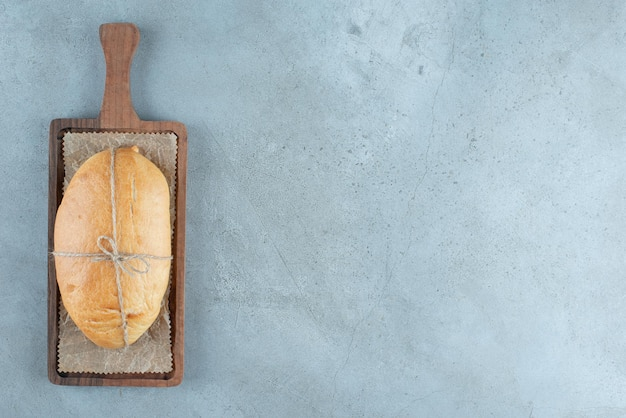 Loaf of bread tied with rope on wooden board.
