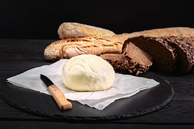 Loaf of bread with butter and knife. dark background, side view.