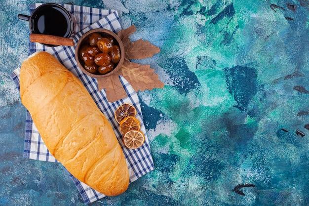 Pagnotta di pane con una tazza di tè e marmellata di frutti di bosco sulla superficie blu.
