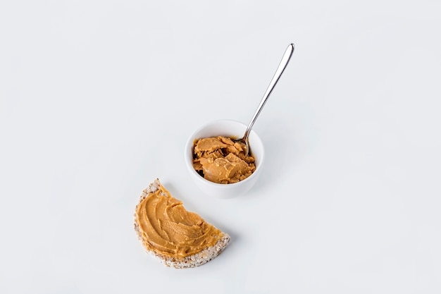 Loaf bread with homemade creamy peanut butter and bowl on white