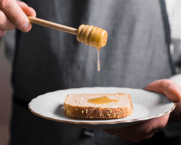 Loaf of bread with honey on plate