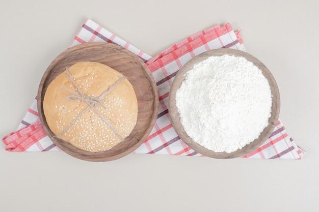 Pagnotta un pane per hamburger in corda con farina sul piatto di legno