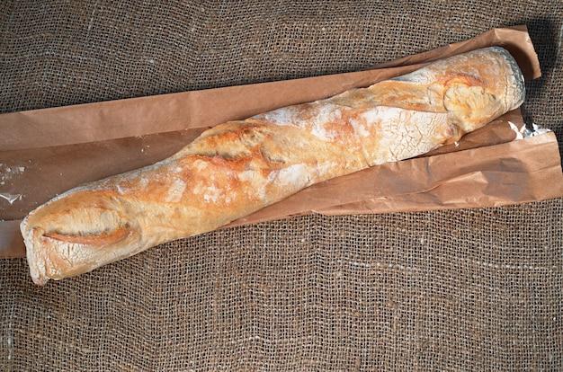 삼베 배경에 덩어리 치아바타 빵과 종이 봉지, 위쪽