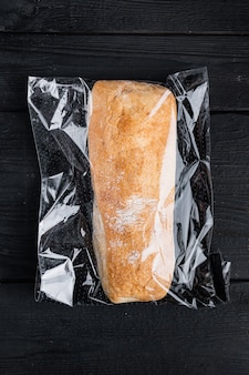 Loaf of fresh baked artisan whole grain ciabatta bread in a market bag, on black wooden table background, top view flat lay