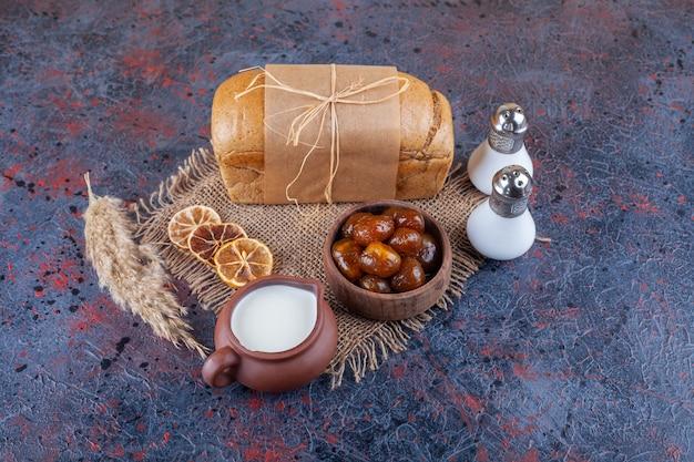 Pagnotta di pane fresco su tela con datteri secchi e latte.