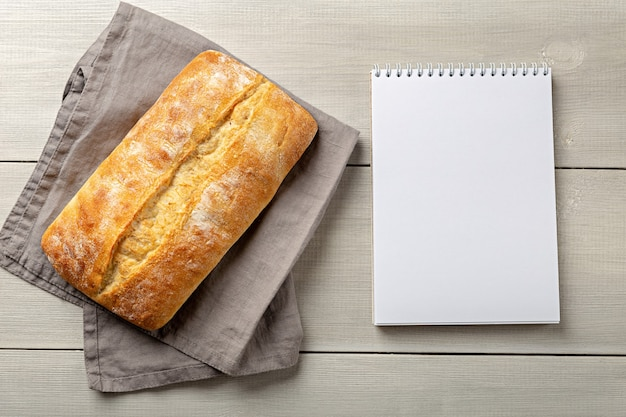 Loaf of fresh bread on gray napkin with notepad top view