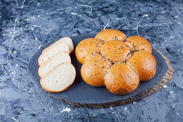 Pagnotta di pane fresco fragrante con fette di pane tostato sul tavolo blu.