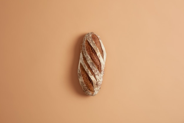 Loaf of fresh homemade crisp french whole grain bread prepared from organic flour, made on leaven, isolated on brown studio background. bakery and food concept. home cooking and food preparation.