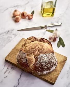 Pagnotta di pane integrale appena sfornato su una tavola di legno con cipolle, aglio, olio e un coltello
