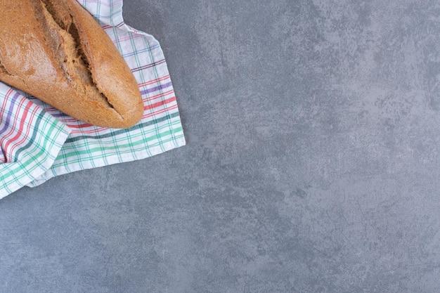 Буханка хлеба дубинки на полотенце на мраморном фоне. фото высокого качества