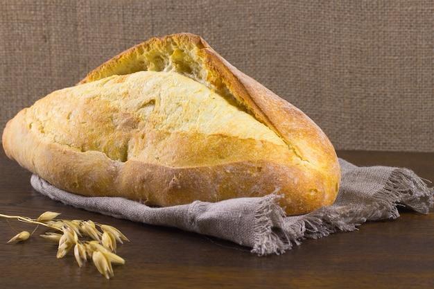 Буханка хлеба и веточка овса на столе