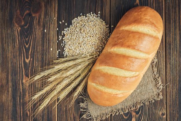 빵 덩어리와 어두운 나무 배경에 곡물의 귀.