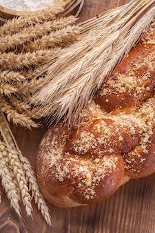 パンのパンとビンテージボード上の小麦リーの耳