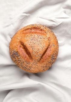 Буханка хлеба на белой льняной ткани