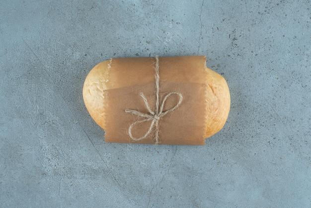 대리석 표면에 밧줄로 묶인 빵 한 덩어리.