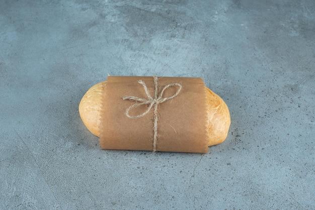 Буханка хлеба, перевязанная веревкой на мраморной поверхности.